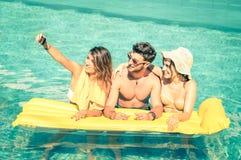 Mejores amigos que toman el selfie en la piscina con colchón neumático amarillo Fotos de archivo libres de regalías