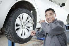 Mekaniker Adjusting Tire royaltyfria bilder