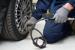 Mekaniker Checking Tyre Pressure med måttet Royaltyfri Foto