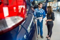 Mekaniker Discussing With Businesswoman med bilen på garaget Arkivfoto