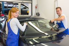 Mekaniker eller glasmästare installerar vindrutan eller vindrutan på bilen Royaltyfri Foto