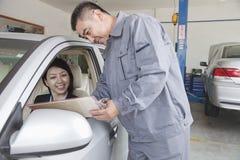 Mekaniker Explaining till affärskvinnan Royaltyfri Fotografi