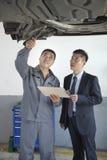 Mekaniker Explaining till affärsmannen Royaltyfri Fotografi