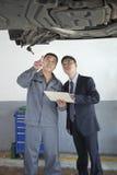 Mekaniker Explaining till affärsmannen royaltyfri bild