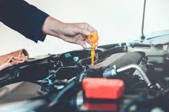 Mekaniker för bilmotorolja som arbetar i service för auto reparation fotografering för bildbyråer