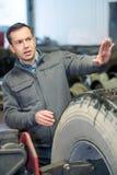 Mekaniker för service för bilgummihjul som ger tecken royaltyfri foto