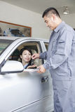 Mekaniker Handing Keys till affärskvinnasammanträde i bil arkivfoto