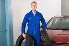 Mekaniker Holding Tires royaltyfri foto