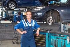 Mekaniker i ett garage som lutar mot en hjälpmedelspårvagn royaltyfria foton