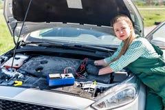 Mekaniker - kvinnaprov bilar med testeren royaltyfri foto