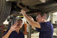 Mekaniker And Male Trainee som tillsammans arbetar under bilen arkivbilder