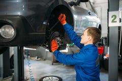 Mekaniker med skiftnyckelreparationer upph?ngningen av bilen royaltyfri fotografi