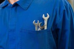 Mekaniker med skiftnycklar i fack royaltyfri foto