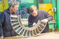Mekaniker monterar delar för flygmotor Arkivbild