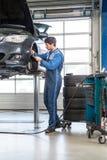 Mekaniker och att arbeta på en bil som kontrollerar tjockleken av bromsen royaltyfria bilder