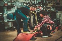 Mekaniker och hans hj?lpreda som reparerar en motorcykel i ett seminarium royaltyfria bilder