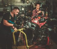 Mekaniker och hans hj?lpreda som reparerar en motorcykel i ett seminarium royaltyfri bild