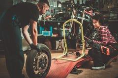 Mekaniker och hans hj?lpreda som reparerar en motorcykel i ett seminarium royaltyfri foto