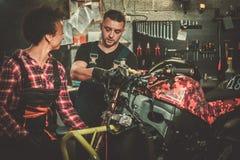 Mekaniker och hans hj?lpreda som reparerar en motorcykel i ett seminarium arkivbilder