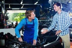 Mekaniker och kund som talar om mopeden arkivbild