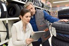 Mekaniker och person som ägnar sig åt handel som använder minnestavlan i billager Fotografering för Bildbyråer