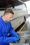 Mekaniker omkring som arbetar på bussen på bussgaraget royaltyfri foto