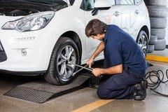 Mekaniker Repairing Car Tire på garaget arkivfoton