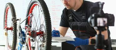 Mekaniker Repairing Mountain Cycle på sportlagret arkivbilder