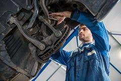 Mekaniker Repairing Suspension System av bilen i garage Arkivfoto