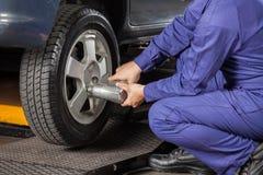 Mekaniker Screwing Car Tire med den pneumatiska skiftnyckeln arkivbild