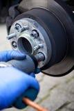 Mekaniker som ändrar ett hjul av en bil royaltyfri fotografi