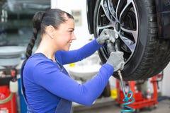 Att ändra för mekaniker rullar på en bil på hydraulisk ramp fotografering för bildbyråer