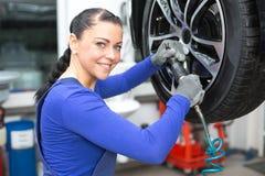 Att ändra för mekaniker rullar på en bil på hydraulisk ramp royaltyfri foto