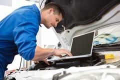 Mekaniker som använder bärbara datorn på bilen arkivbild