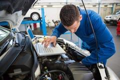 Mekaniker som använder bärbara datorn på bilen royaltyfri fotografi
