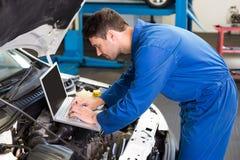 Mekaniker som använder bärbara datorn på bilen arkivfoton