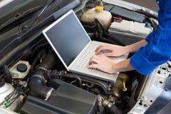 Mekaniker som använder bärbara datorn på bilen royaltyfria bilder