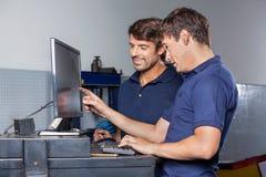 Mekaniker som använder datoren i garage fotografering för bildbyråer