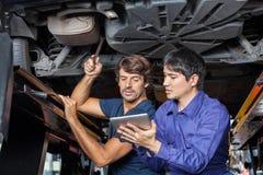 Mekaniker som använder den Digital minnestavlan under lyftbilen arkivfoto