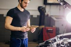 Mekaniker som använder den digitala minnestavlan bredvid en öppen huv i garage arkivfoto