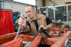 Mekaniker som använder den stora skruvnyckeln arkivfoton