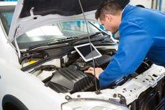 Mekaniker som använder minnestavlan för att fixa bilen arkivfoton