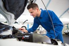 Mekaniker som använder minnestavlan för att fixa bilen royaltyfri foto