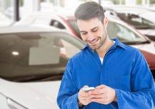 Mekaniker som använder mobiltelefonen i parkeringsplats royaltyfria bilder