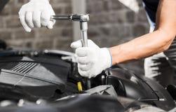 Mekaniker som arbetar i garage för auto reparation Bilunderhåll royaltyfri foto