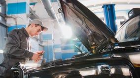 Mekaniker som arbetar i garaget - reparera lyxiga SUV framme av solen arkivbilder