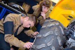 Mekaniker som arbetar på hjulbarnvagnen arkivbild