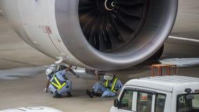 Mekaniker som arbetar på jetmotorn på grov asfaltbeläggning fotografering för bildbyråer