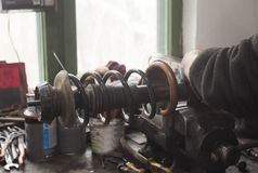 Mekaniker som arbetar på stötdämparen för använd bil royaltyfri bild
