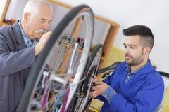 Mekaniker som arbetar p? cykelhjulet arkivbilder